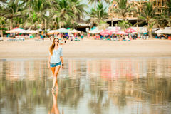 Beautifil young woman walking along the beach at Royalty Free Stock Images