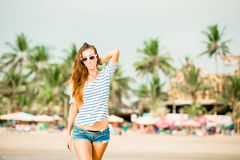 Beautifil young woman walking along the beach at Stock Images