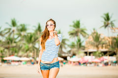 Beautifil young woman walking along the beach at Stock Photography