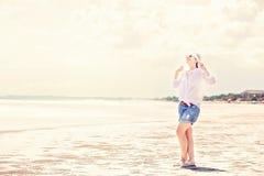 Beautifil young woman walking along the beach at Royalty Free Stock Image