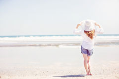 Beautifil young woman walking along the beach at Royalty Free Stock Photos