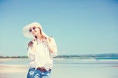 Beautifil young woman walking along the beach at Royalty Free Stock Photo