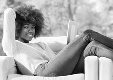 Beautifl black girl lying on couch stock photos