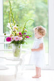 Beautifl toddler girl watching flowers in a big vase Stock Photos