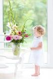 Beautifl toddler girl watching flowers in a big vase Stock Photos