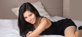 Beautifu Asian model wearing black dress. Posing on bed stock photography