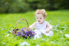 Beautifu baby girl with blond curly hair wearing a white dress. Plaing on meadow Stock Photography