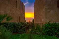 A beautifu and colorful sunset at sea in between two buildings and a garden. Royalty Free Stock Image