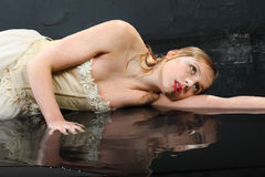 Beautifu girl lies on wet floor Royalty Free Stock Images