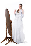 Beautifu happy woman chosing and try on wedding dress near the mirror Royalty Free Stock Photography