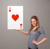 Beautifu woman holding a red heart ace. Beautifu young woman holding a red heart ace Royalty Free Stock Images