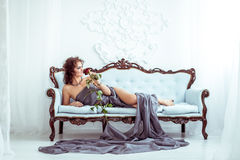 Beautifu woman lying on couch and holding red rose Stock Photos