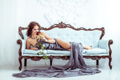 Beautifu woman lying on couch and holding red rose Royalty Free Stock Images