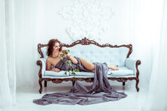 Beautifu woman lying on couch and holding red rose Royalty Free Stock Image