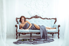 Beautifu woman lying on couch and holding red rose Stock Image