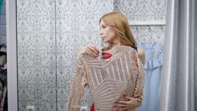 Beautifuil blonde woman trying on clothes in a dressing room in a boutique. She is holding a beautiful dress. Closing curtrain stock video