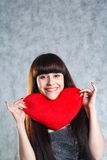 Beautiful 20-25 years young brunette woman. Holding red heart pillow on grey background stock photo