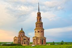 Beautiful abandoned Trinity Church and bell tower in the Russian Village Novotroitskoye, Lipetsk region. On sunset cloudy sky background stock images