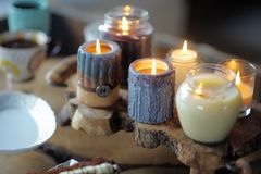 Beautiful ablaze candle. On the wooden table Stock Photo