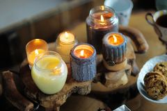 Beautiful ablaze candle. On the wooden table Stock Photos