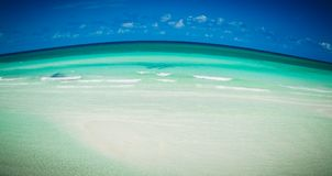 Beautiful abstract view of tropical beach with rising curved ocean and dark blue sky background. Abstract amazing view of tropical beach with rising curved ocean royalty free stock photos