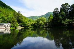 Beautiful abundant natural green mountain landscape symmetrical reflection on fresh lake Kinrin with blue sky background. During springtime, Yufuin, Japan Stock Photography
