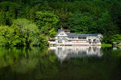 Beautiful abundant natural green mountain plant reflection on fresh lake Kinrin with buildings during springtime. Yufuin, Japan royalty free stock image