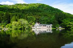 Beautiful abundant natural green mountain slope reflection on fresh lake Kinrinko with buildings during springtime. Yufuin, Japan royalty free stock images