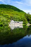 Beautiful abundant natural shades of spring green mountain background mirror reflection on fresh lake Kinrinko with buildings. And blue sky, Yufuin, Japan royalty free stock image