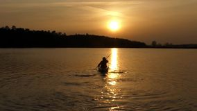 Beautiful action at sunset, the man sail on canoe in the lake. stock footage