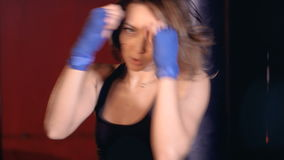 Beautiful active athletic woman boxing in fitness studio. Woman strength concept.