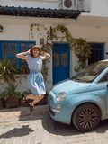 Beautiful active redhead young woman wearing blue dress and jumping on street in front of retro car royalty free stock photo