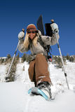 Beautiful active woman with snowshoes and snowboard