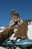 Beautiful active woman with snowshoes and snowboard prays. A beautiful active woman ready to hike in the mountains with snowshoes and snowboard prays for snow royalty free stock image