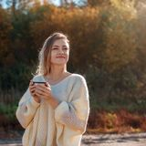 Beautiful admiring woman drinking hot tea from thermos cup royalty free stock images