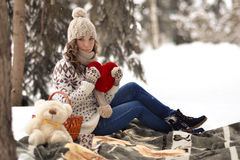 Attractive,beautiful,cute,pretty girl hold toy,girl with big,red heart in her hands,sit in warm plaid,has picnic in winter forest Stock Photography