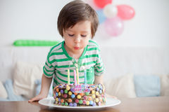 Beautiful adorable four year old boy in green shirt, celebrating. His birthday, blowing candles on homemade baked cake, indoor. Birthday party for kids Royalty Free Stock Photo