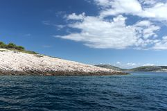 Beautiful Adriatic sea islands. Beautiful day on Adriatic Sea; rippled surface of clean sea water with white rocks of Mišjak island and blue, cloudy royalty free stock images