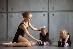 Ballerina teach girls. A beautiful adult blonde Russian ballerina in a black tutu and white pantyhose helps to stretch two little girls to ballerinas Royalty Free Stock Image