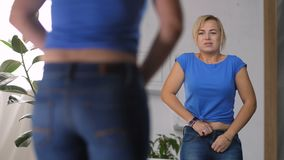 Adult woman struggling to zip up too tight jeans