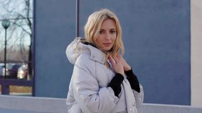 Beautiful adult blonde woman is wearing warm trendy down jacket, standing outdoors in city in sunny autumn day. Looking at camera stock video footage