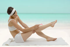 Beautiful adult caucasian woman shaving legs with razor Royalty Free Stock Image