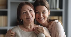 Beautiful adult daughter hugging older mature mum looking at camera