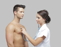 Beautiful adult doctor examining a men Stock Images