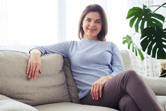 Beautiful adult female sitting on sofa in bright living room Royalty Free Stock Photo