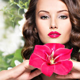 Beautiful adult girl with bright red lips and flower near the fa. Portrait of young beautiful adult girl with bright red lips and flower near the face - creative Stock Photo