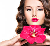 Beautiful adult girl with bright red lips and flower near the fa Royalty Free Stock Photos