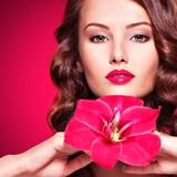 Beautiful adult girl with bright red lips and flower near the fa. Portrait of young beautiful adult girl with bright red lips and flower near the face -  on pink Royalty Free Stock Image
