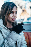 Beautiful adult girl drinking Martini outdoor , early spring. Young woman drinking martini in a cold weather outdoor Royalty Free Stock Photo