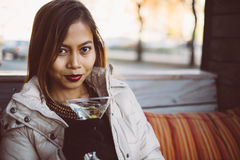 Beautiful adult girl drinking Martini outdoor , early spring. Young woman drinking martini in a cold weather outdoor Stock Photo